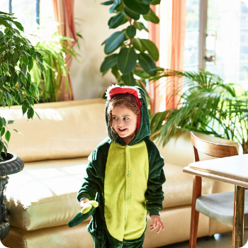 A small child in a dinosaur onesie in a living room setting - contact Claro