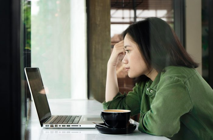 Woman sat working at a desk looking frustrated - learn more about money with Claro