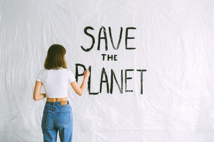 girl writing save the planet on a wall