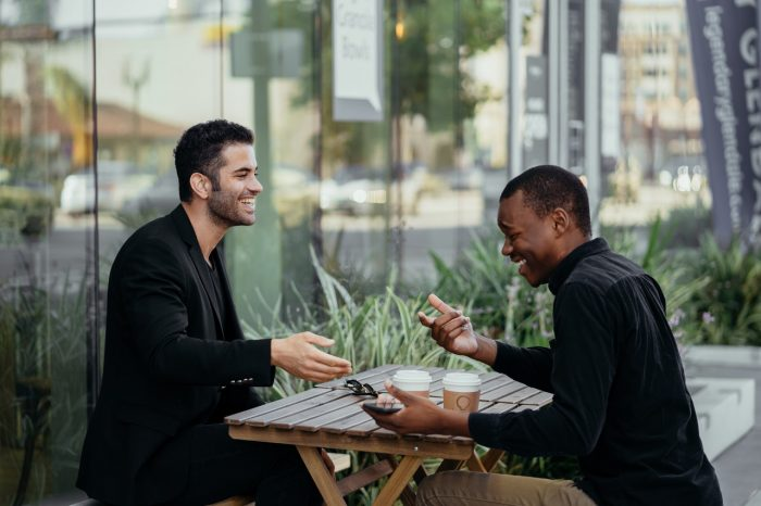 Two men sat laughing at a table outside - get in touch with Claro