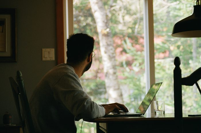 Man at home working on a laptop - protect your finances during coronavirus