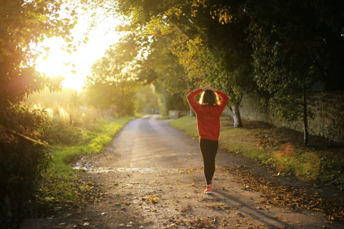 Woman walks along a path, with her hands on her head, indicating that she is stressed.