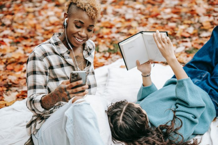 happy woman listening to music on her phone while another reads a book