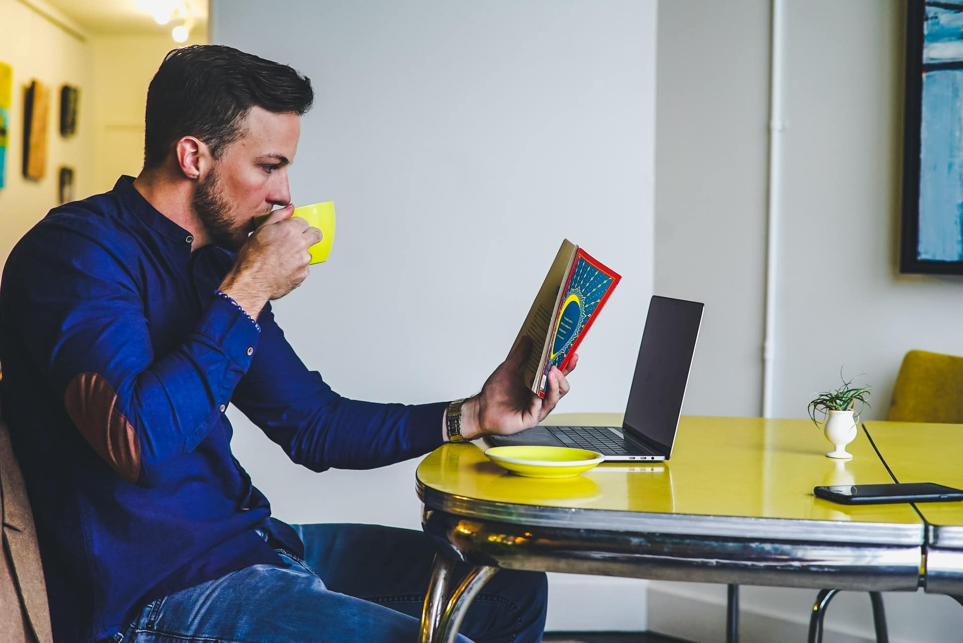 Man drinking coffee reading a book by his laptop