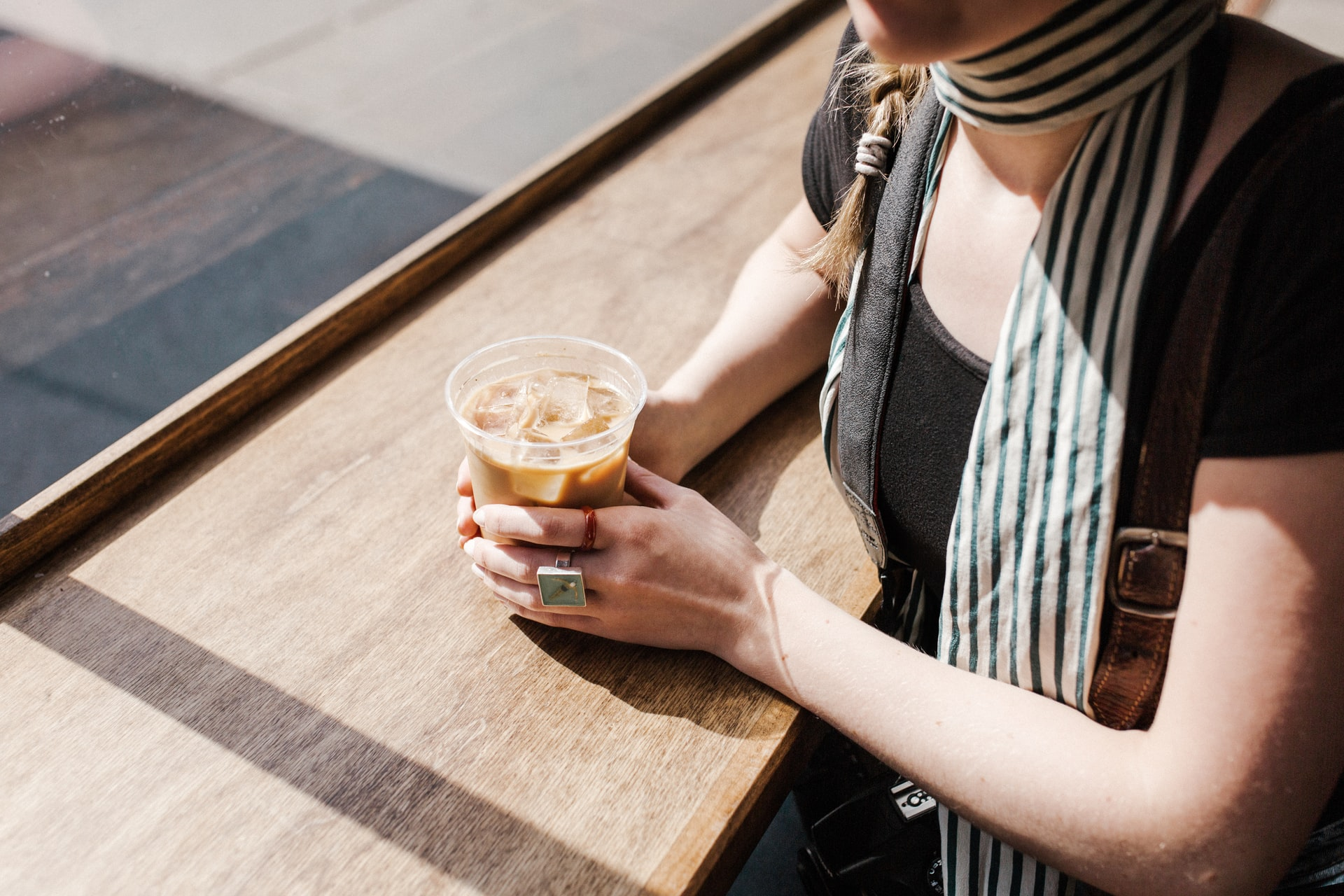 Woman holding coffee in cafe window